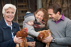 Family with chicken birds standing in poultry farm, Bavaria, Germany