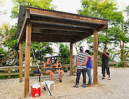 South Merrick, New York, U.S. 14th July 2013. JENNIFER HERNANDEZ from Franklin Square, at extreme left, and LUIS HERRERA from the Brronx, at extreme right, are 2 of 5 friends who, after fishing at the Levy Park & Preserve fishing pier, waited under a rustic wood overhang shelter for a Park Ranger to pick them up in a jitney. As National Weather Service extended its Heat Advisory in Long Island, New York, through to next day, South Shore winds helped those at park cope with the dangerous heatwave spreading throughout the Northeast, 92 degrees Fahrenheit, 33 degrees Celsius.
