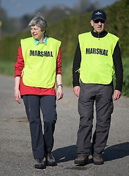 © Licensed to London News Pictures. 19/04/2019. Maidenhead, UK. Prime Minister THERESA MAY  helps out as a marshal with her husband PHILIP MAY at the Maidenhead Easter 10 run in her constituency of Maidenhead in Berkshire. Parliament currently on Easter recess after an extension to Article 50 was granted by the EU. Photo credit: Ben Cawthra/LNP