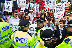 "Cricklewood, London, July 19th 2014. Anti-fascists are held in check by police as they heavily outnumber 13 anti-Islamists from the ""South East Alliance"" as they demonstrate outside the London offices of Egypt's Muslim Brotherhood."