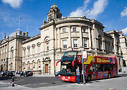 Red double decker open topped sightseeing bus by the Guildhall, Bath, Somerset, England