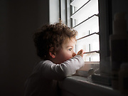Two year old toddler looks out of the window