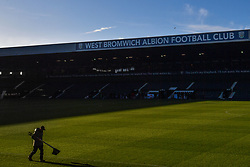 A groundsman carries corner flags at The Hawthorns