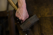A blacksmith holds a sledgehammer in an metal work shop in Charleston, SC