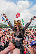 Entertained by trying to catch a fiver dangling on a string, fans were in good spirits wile awaiting Madness at the Pyramid Stage - The 2016 Glastonbury Festival, Worthy Farm, Glastonbury.