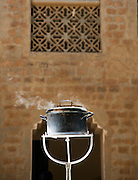 A pot of water boils in the reflected heat of the sun, using Solar Cooker, in Djenné, Mali
