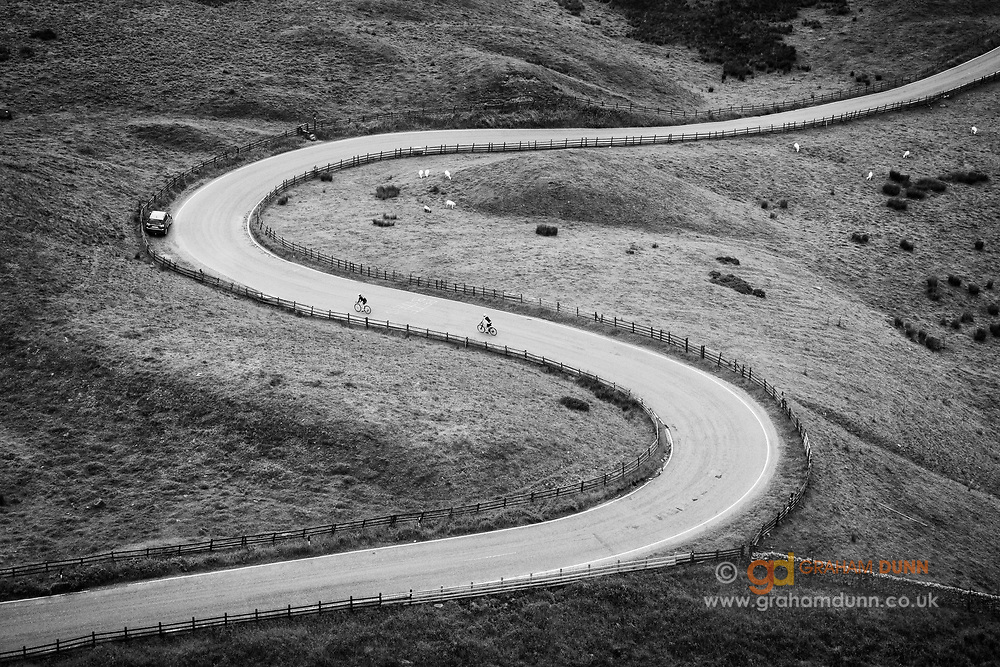 Two cyclists enjoy the winding decent through Mam Nick to Edale in the Peak District. A stunning section of road that winds through the undulations caused by an ancient landslip from Rushup Edge. Captured from the slopes of Mam Tor in the Derbyshire Peak District, England, UK. Commended, Landscape Photographer of the Year 2016.