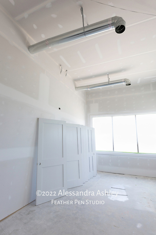 Doors are prepared for painting and installation while wall priming progresses at building site of new physical therapy and wellness center.