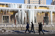ALTAY, CHINA - JANUARY 12: (CHINA OUT) <br /> <br /> Citizens pass by a row of houses whose eaves are hung with icefalls as the snow melts on daytime and freezes at night on January 12, 2016 in Altay Prefecture, Xinjiang Uyghur Autonomous Region of China. Affected by El Nino Phenomenon, Altay Prefecture seems to be a warm winter this year compared with previous winters. <br /> ©Exclusivepix Media