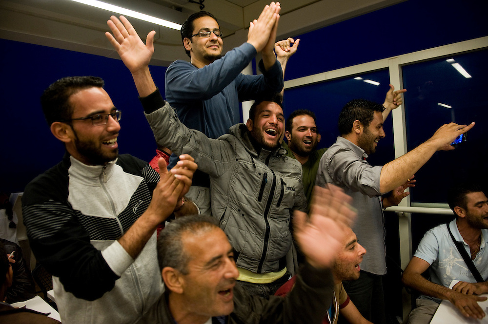 A group of Syrian refugees celebrating their rescue after their have been given temporary traveling documents onboard the Lesbos to Piraeus boat. The boat was full of refugees heading to mainland Greece. Everyday hundreds of refugees, mainly from Syria and Afghanistan, are crossing in small overcrowded inflatable boats the 6 mile channel from the Turkish coast to the island of Lesbos in Greece.