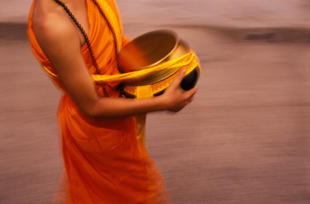 A novice monk carries a food bowl during a morning alms walk in the streets of Mae Hong Son, Thailand. April 2003. People will put food into the bowl as an offering, thereby gaining religious merit.