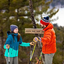 A couple takes a break from snowshoeing near the summit of Bald Pate Mountain at Loon Echo Land Trust's Bald Pate Mountain Preserve in South Bridgton, Maine.