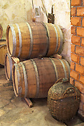 Old oak barrels and an old demijohn in a wicker basket in the wine cellar. Matusko Winery. Potmje village, Dingac wine region, Peljesac peninsula. Matusko Winery. Dingac village and region. Peljesac peninsula. Dalmatian Coast, Croatia, Europe.