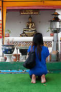 Wat Po Temple of the Reclining Buddha Bangkok Thailand prating in the temple