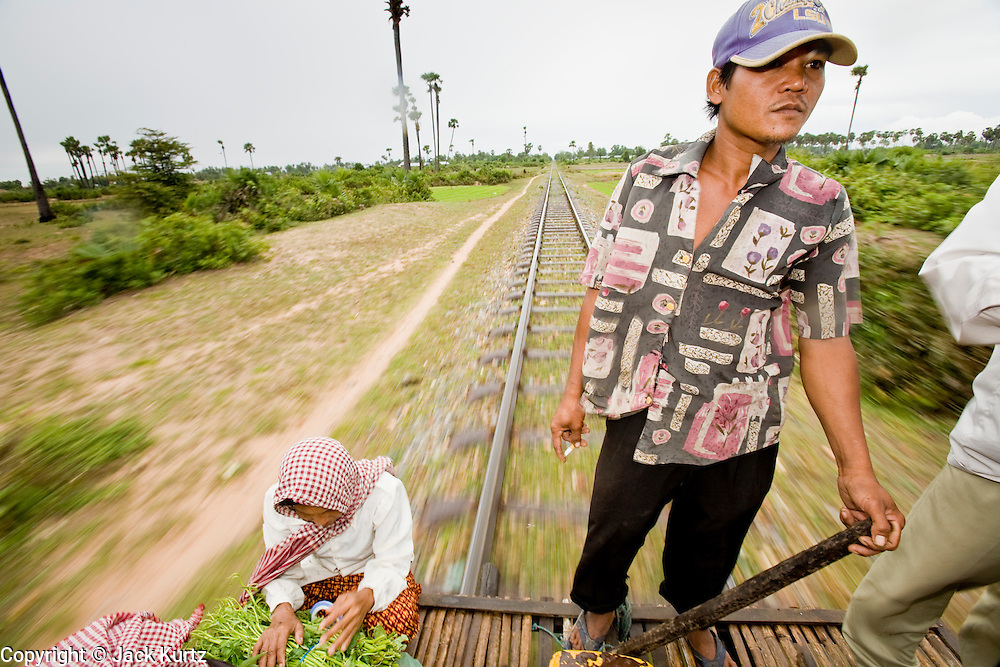 """01 JULY 2006 - PHNOM PENH, CAMBODIA: A man drives a bamboo train in central Cambodia. The """"bamboo trains"""" run along the government tracks in rural Cambodia. Bamboo mats are fitted over wheels which ride on the rails. The contraption is powered by a either a motorcycle or lawn mower engine. The Cambodian government would like to get rid of the bamboo trains, but with only passenger train in the country, that runs only one day a week, the bamboo trains meet a need the government trains do not. While much of Cambodia's infrastructure has been rebuilt since the wars which tore the country apart in the late 1980s, the train system is still in disrepair. There is now only one passenger train in the country. It runs from Phnom Penh to the provincial capitol Battambang and it runs only one day a week. It takes 12 hours to complete the 190 mile journey.  Photo by Jack Kurtz / ZUMA Press"""