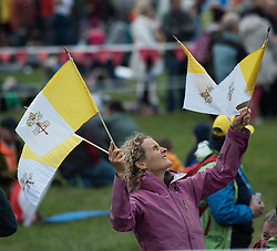 © Licensed to London News Pictures. 26/08/2018. Dublin, Ireland. A woman waves the papal flag as crowds gather in wet weather during the visit of Pope Francis to Phoenix Park Dublin. Pope Francis said mass to an estimated hundred thousand people. Pope Francis is the 266th Catholic Pope and current sovereign of the Vatican. Photo credit: Barry Cronin/LNP