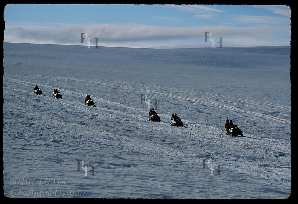 Line of snowmobiles speeds down slope atop Vatnajokull glacier during a two-hour Glacier Tours trip; southeast Iceland.