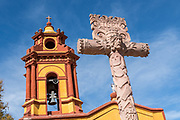 The Parroquia San Sebastian church with decorative cross and bell tower in the beautiful colonial village of Bernal, Queretaro, Mexico. Bernal is a quaint colonial town known for the Pena de Bernal, a giant monolith which dominates the tiny village is the third highest on the planet.