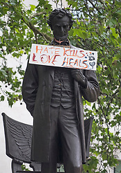 """© Licensed to London News Pictures. 08/06/2020. London, UK. A sign reading """"HATE KILLS, LOVE HEALS"""" hung around a statue of former U.S President Abraham Lincoln in Parliament Square, during a Black Lives Matter demonstration In central London. The death of George Floyd, who died after being restrained by a police officer In Minneapolis, Minnesota, caused widespread rioting and looting across the USA. Photo credit: Ben Cawthra/LNP"""