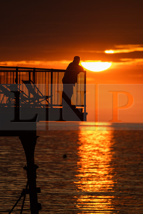 ©Licensed to London News Pictures. 04/07/2019. Aberystwyth, UK. A flat calm sea at sunset in Aberystwyth on the Cardigan Bay coast, west Wales. Photo credit: Keith Morris//LNP