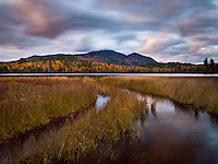fast moving clouds catch the last light of day as autumn foliage graces the slopes of Whiteface mountain in the adirondacks, new york