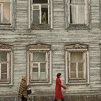 Russian women walk below an ornately carved log building in the northern port city of Arkhangel'sk.
