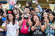 Visitors gets ready to take pictures as a parade approaches at Walt Disney Co.s Shanghai Disneyland theme park  towards the iconic castle during a trial run ahead of its official opening, in Shanghai, China, on Wednesday, June 8, 2016. The $5.5 billion Shanghai Disneyland is one  of the most profitable Disney ventures in the world and the first theme park on mainland China.