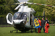 MD902 Explorer helicopter crew from the Kent, Surrey & Sussex Air Ambulance Trust on the ground in Ruskin Park after emergency flight to Kings College Hospital in south London. The flight medical crew load the stretcher used previously for the patient, back ito the aircraft. The Air Ambulance (KSSAAT) fly state of the art Helicopter Emergency Medical Service (HEMS) aircraft operating 365 days a year, out of their base at Marden in Kent and Redhill in Surrey. They're capable of delivering our crews anywhere in our region in under 20 minutes flying time, attending over 20,000 missions