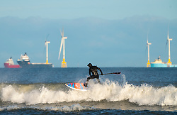 Aberdeen, Scotland, UK. 1st December 2019. Surfers took advantage of bright sunshine and favourable winds creating good waves along the beach at Aberdeen. In the distance are wind turbines of the European Offshore Wind Deployment Centre wind farm. Iain Masterton/Alamy Live News.