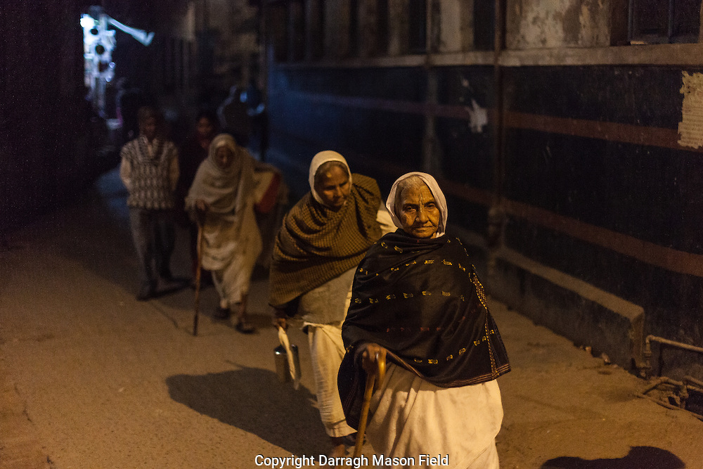 Elderly widows file home after the days  chanting.  Beneath their shawls they wear the white sari's of mourning.