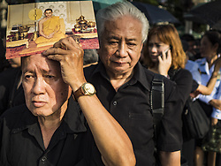 October 14, 2016 - Bangkok, Bangkok, Thailand - A man holds a portrait of the King while he stands in line to enter the Grand Palace in Bangkok to pay respects to Bhumibol Adulyadej, the King of Thailand, who died Oct. 13, 2016. He was 88. His death comes after a period of failing health. With the king's death, the world's longest-reigning monarch is Queen Elizabeth II, who ascended to the British throne in 1952. Bhumibol Adulyadej, was born in Cambridge, MA, on 5 December 1927. He was the ninth monarch of Thailand from the Chakri Dynasty and is known as Rama IX. He became King on June 9, 1946 and served as King of Thailand for 70 years, 126 days. He was, at the time of his death, the world's longest-serving head of state and the longest-reigning monarch in Thai history. (Credit Image: © Jack Kurtz via ZUMA Wire)