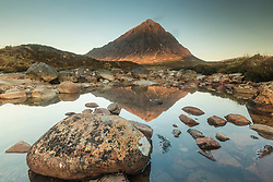 The famous Buachaille Etive Mor reflected in ponds of the River Coupall at sunrise. The mountain provides a stunning entry into Glen Coe