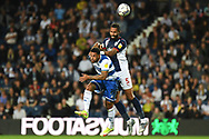 West Bromwich Albion defender Kyle Bartley (5) heads the ball  under pressure from QPR forward (on loan from Watford) Andre Gray (19) during the EFL Sky Bet Championship match between West Bromwich Albion and Queens Park Rangers at The Hawthorns, West Bromwich, England on 24 September 2021.