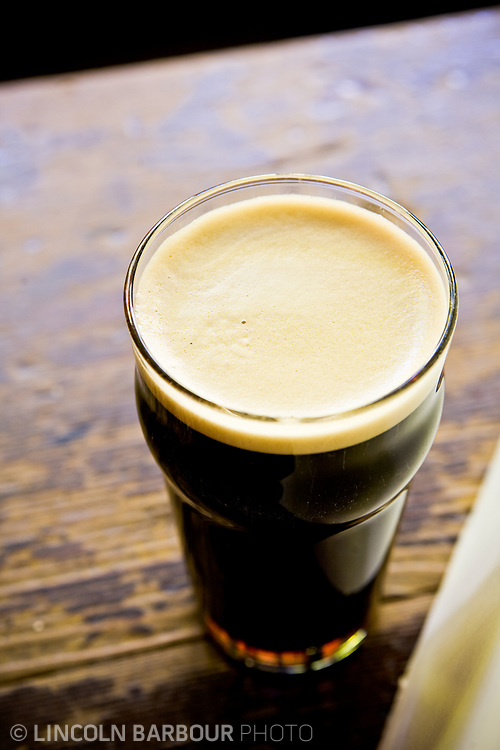 A top down view of a freshly poored pint of beer.  Dark in color, set on a wooden bar or table.