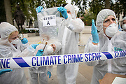 Extinction Rebellion 'crime scene investigators' in white suits and masks put up climate crime scene tape to investigate areas of ecocide and find 'Exhibit A' in a performance in Parliament Square in an area already cordoned off on 7th September 2020 in London, United Kingdom. The 20 investigators were protesting at the UK government's ecocide along the HS2 route. Extinction Rebellion is a climate change group started in 2018 and has gained a huge following of people committed to peaceful protests. These protests are highlighting that the government is not doing enough to avoid catastrophic climate change and to demand the government take radical action to save the planet.