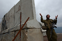 TZIPOREN, ISRAEL, MARCH 2:An Israeli soldier gestures to journalists next to the border with Lebanon near Tziporen army base in north Israel, Sunday, March 2, 2003 as Hezbollah Shiite militants watch from the other side of the fence.  <br />(Ami Vitale/Getty Images)