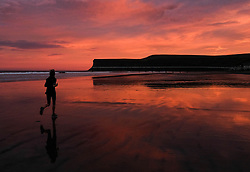 © Licensed to London News Pictures. <br /> 23/12/2016. <br /> Saltburn-by-the-Sea, UK.  <br /> <br /> A woman enjoys a morning run as the first light of dawn illuminates the sky over the beach at Saltburn by the Sea as the UK braces itself for the arrival of Storm Barbara.<br /> Severe weather warnings are in place across the country with winds of up to 90mph expected in some areas.<br /> <br /> <br /> Photo credit: Ian Forsyth/LNP