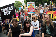 Peoples Assembly National Demonstration Against Theresa May and Austerity - Not One Day More - Tories Out arrives at Downing Street where protesters sit down in the road, on Saturday July 1st in London, United Kingdom. Tens of thousands of people gathered to protest in a march through the capital protesting against the Conservative Party cuts. Following the recent General Election where the Labour Party gained seats, while the Conservative Party lost their majority, the mood in the country has been one where an anti-austerity movement is growing as people become tired with Tory rule.