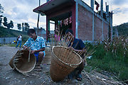 Wicker basket making at dusk near Dhading. The basket is used for many things and usually carried on the back with a strap around the fore head.