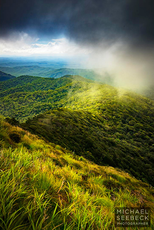 Heavy clouds roll over in over a rainforested ridge connected to Kalpahlim Rock, in Far North Queensland.<br /> <br /> Limited Edition Print