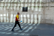 During the Coronavirus pandemic, a DHL courier wearing surgical gloves walks beneath the Monument in the City of London, the capital's financial district, on 29th July 2020, in London, England.