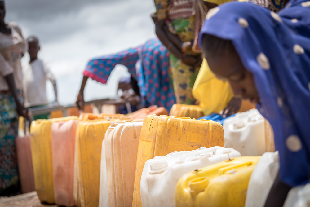 30 May 2019, Mokolo, Cameroon: Women queue to fill up their jerry cans with drinking water at one of the tapstands in Minawao camp. The Minawao camp for Nigerian refugees, located in the Far North region of Cameroon, hosts some 58,000 refugees from North East Nigeria. The refugees are supported by the Lutheran World Federation, together with a range of partners.