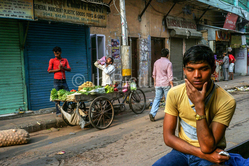 A vegetable vendor takes a drink from a plastic bag at dawn in Sitaram Bazar, Old Delhi, India.