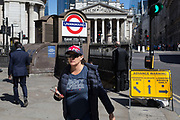 A woman wears a Union Jack cap outside one entrance of Bank Underground Station in the City of London, the capitals ancient, financial district, on 14th May, in London, England.