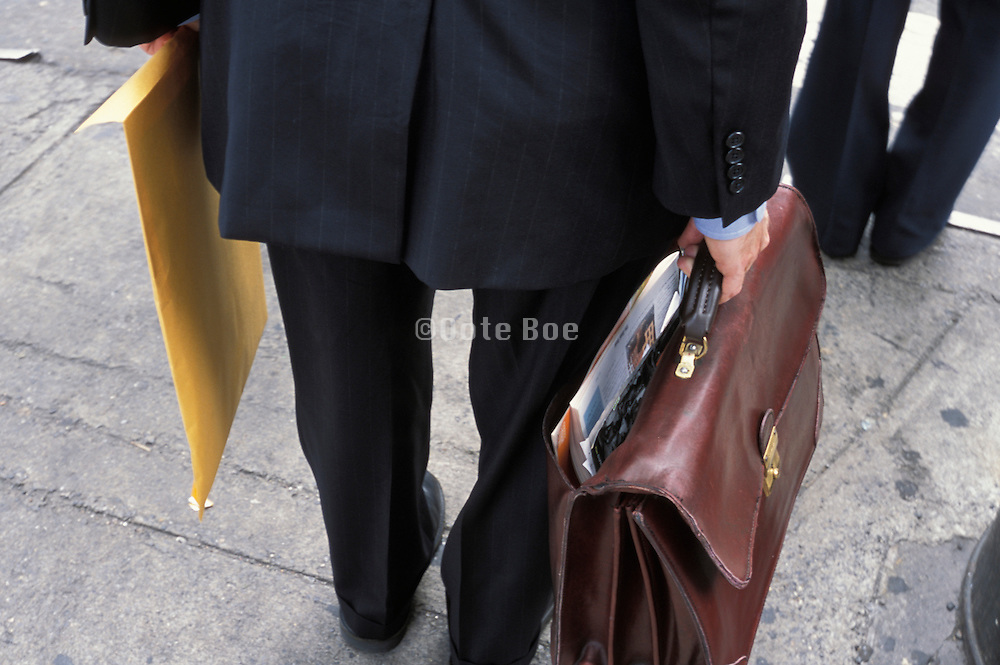 Business man with a folder and a briefcase standing on site of street
