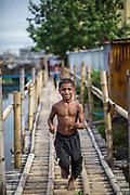 """A boy runs across a bridge at the entrance to a """"slum"""" district"""