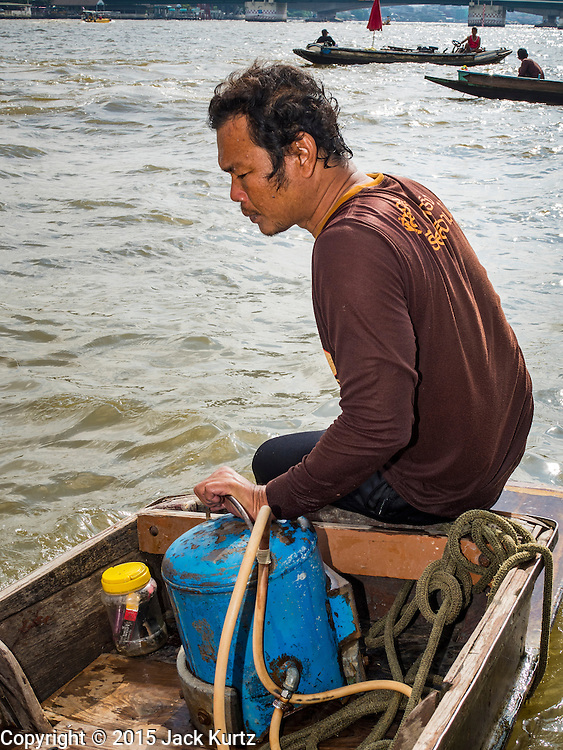 14 OCTOBER 2015 - BANGKOK, THAILAND:  A diver rests with his hand on his dive helmet during a break in diving in the Chao Phraya River in Bangkok. Divers work in two man teams on small boats in the Chao Phraya River. One person stays in the boat while the diver scours the river bottom for anything that can be salvaged and resold. The divers usually work close to shore because the center of the river is a busy commercial waterway with passenger boats and commercial freight barges passing up and down the river all day long. The Chao Phraya is a dangerous river to dive in. It's deep, has large tidal fluctuations, is fast flowing and badly polluted. The divers make money only when they sell something.   PHOTO BY JACK KURTZ