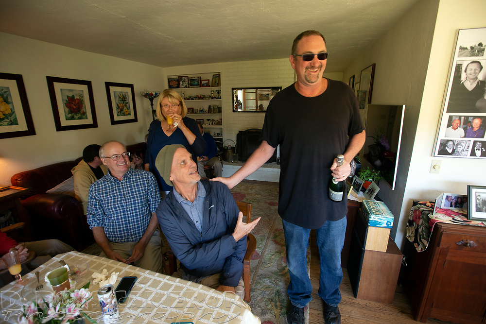 Noah Berger, right, greets guests at a party celebrating the 80th birthday of long-time Oakland Tribune photographer Ron Riesterer, Sunday, Oct. 21, 2018 in Oakland, Calif. (Photo by D. Ross Cameron)