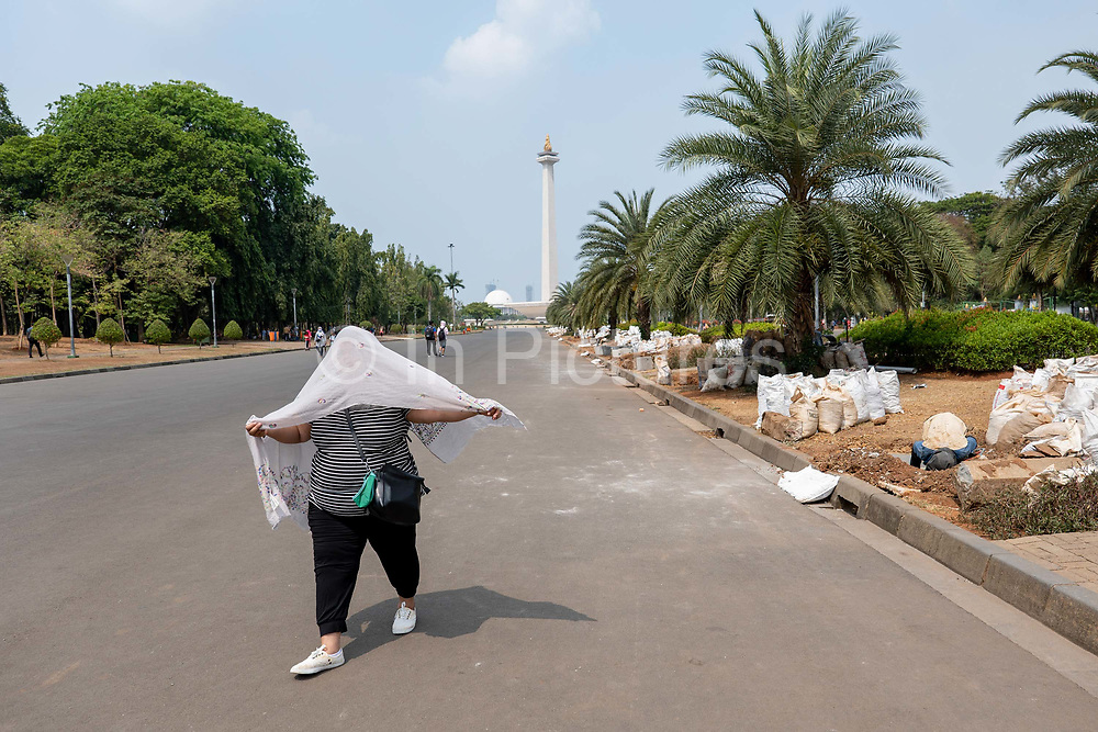 A lady covering her face from the sun at Merdeka Square with the National Monument in the horizon on the 2nd November 2019 in Java in Indonesia.