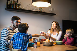 Mother is offering bread to her son while family watches, Munich, Germany